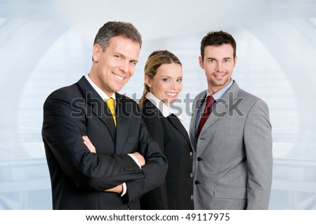 Three happy business colleagues standing together and looking at camera in their modern office - stock photo