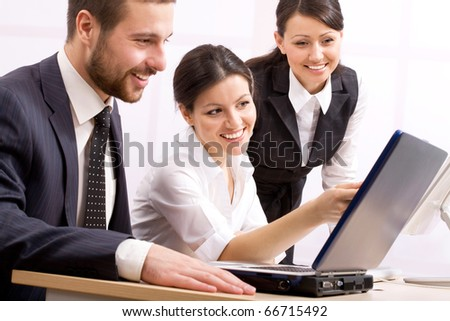 Three happy business people in a meeting at office - stock photo