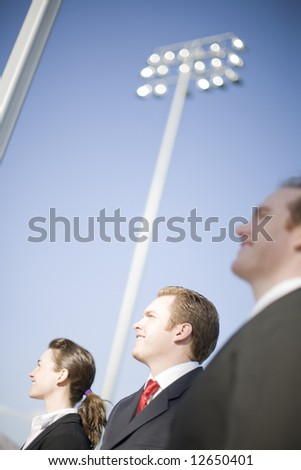 three happy business people standing and smiling with big lights behind in background - stock photo