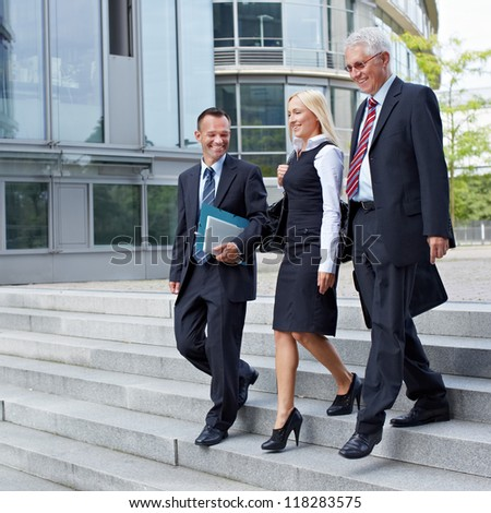 Three happy business people walking together outside - stock photo