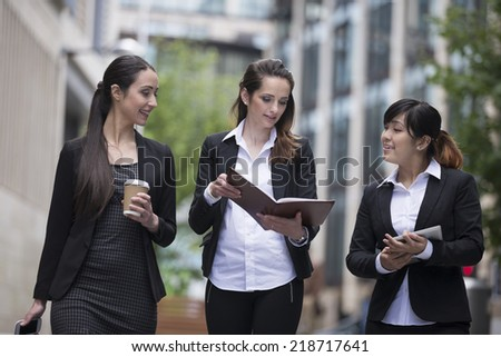 Three Happy Business women walking outside and talking to each other. - stock photo