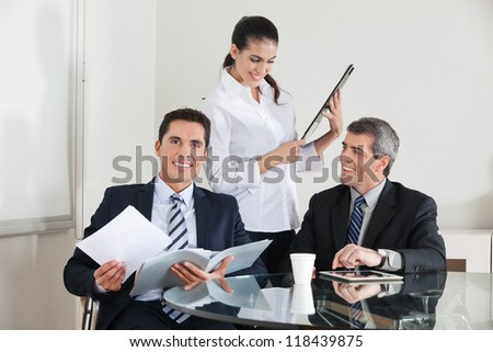 Three happy businesspeople working together in the office - stock photo