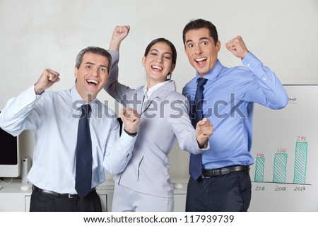 Three happy cheering businesspeople with clenched fists in the offce - stock photo