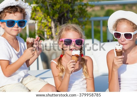 Three happy children eating ice cream near swimming pool at the day time. Concept healthy food.