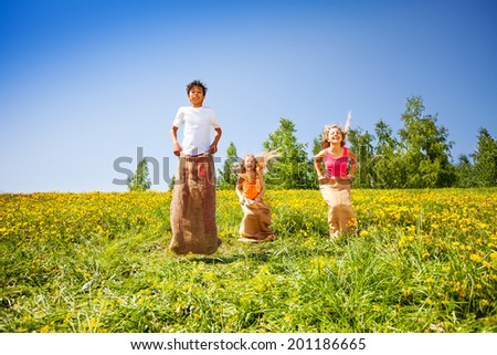Three happy children jumping in sacks during play - stock photo