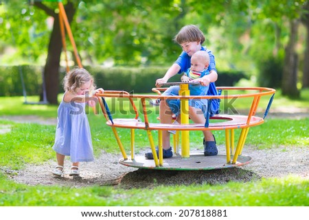 Three happy children, laughing teenager boy, cute baby and adorable toddler girl, brothers and sister playing together on a playground swing enjoying a sunny hot summer day - stock photo