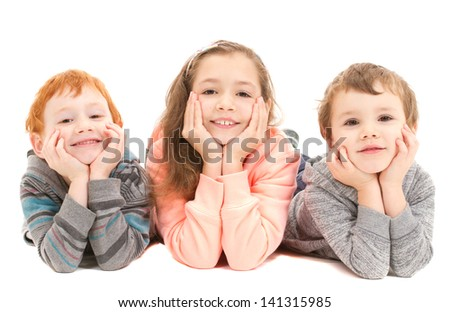 Three happy children laying on floor resting head on hands. On white.