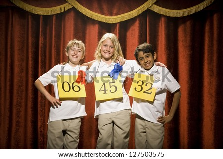 Three happy children on stage at winner's podium with ribbons - stock photo