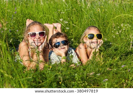 Three happy children  playing near the tree at the day time. Concept Brother And Sister Together Forever
