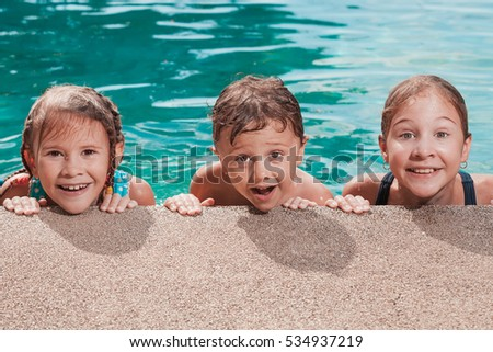 Three happy children playing on the swimming pool at the day time. People having fun outdoors. Concept of friendly siblings.
