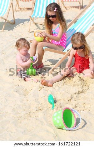 Three happy children sit on beach and play with toys at sunny summer day. - stock photo