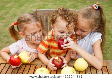 three happy children sitting at the table and eat apples - stock photo