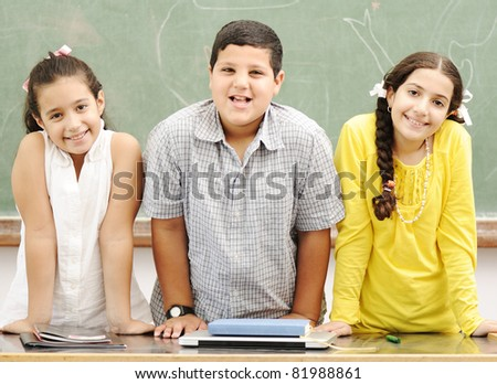 Three happy children standing at board, posing beside the table - stock photo