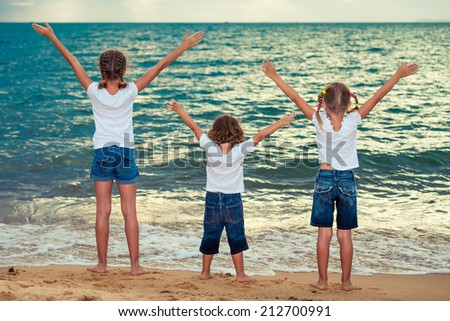 Three happy children standing on the beach at the evening time - stock photo