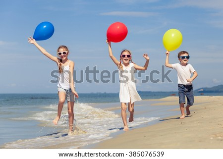Three happy children with balloons playing on the beach at the day time. Concept of happy friendly family. - stock photo
