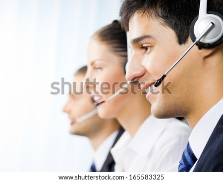 Three happy customer support phone operators at office - stock photo