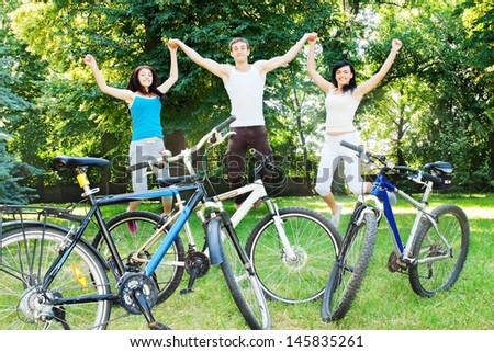 Three happy cyclists jumping in the park - stock photo