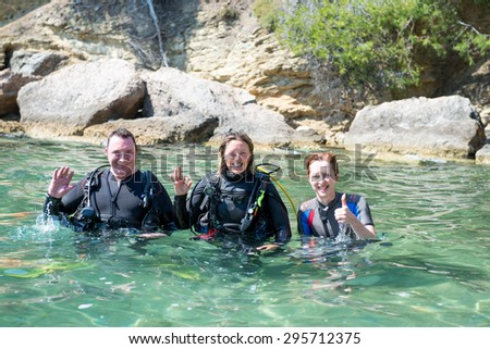 Three happy divers standing in shallow water before a dive.two of them are wearing their scuba equipment. - stock photo