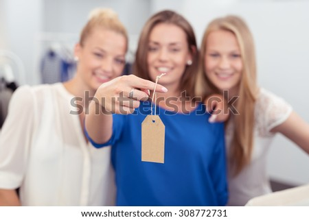 Three Happy Female Friends in a Clothing Shop Showing a Blank Brown Tag for Texts at the Camera in Close up.