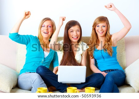 Three happy friends beautiful girls sitting on sofa in home with laptop computer, with hands up celebrating success - stock photo