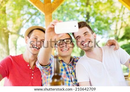 Three happy friends drinking and taking selfie with smartphone in pub garden
