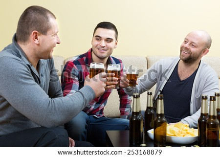 Three happy friends drinking beer and talking at home  together - stock photo