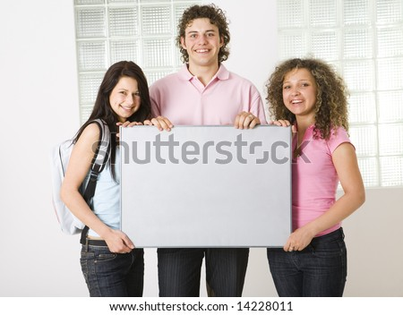 Three happy friends holding grey table. Looking at camera. Front view. - stock photo