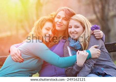 Three happy friends in the park - stock photo