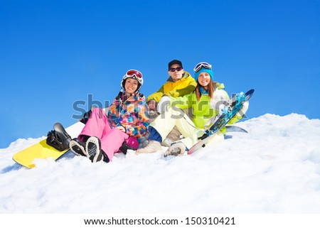 Three happy friends man and women sit in snow with snowboards lifting and waving hands