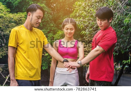 Three happy friends  putting their hands together in the park