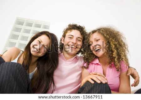 Three happy friends sitting and looking at camera. Low angle view. - stock photo