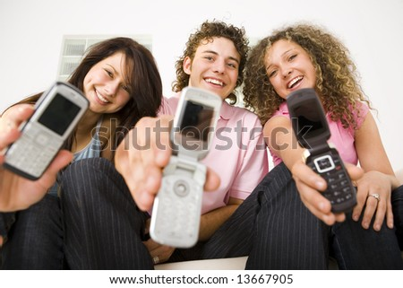 Three happy friends sitting and showing mobile phone to the camera. Looking at camera. Low angle view. - stock photo