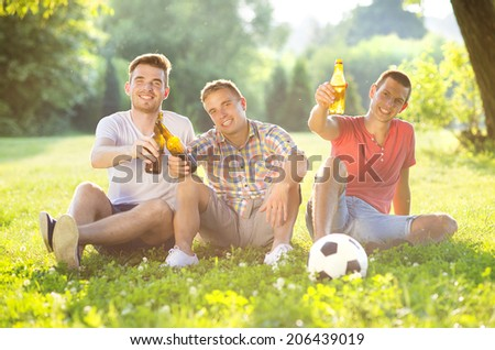 Three happy friends spending free time together in park sitting on grass, drinking beer and chatting - stock photo