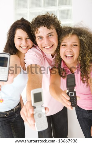 Three happy friends standing and showing mobile phone to the camera. Looking at camera. Low angle view. - stock photo