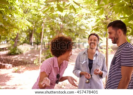 Three happy friends telling funny stories and laughing together in the dappled afternoon sunshine with some trees around them wearing casual clothing