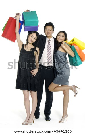 three happy friends with shopping bags standing in the studio - stock photo