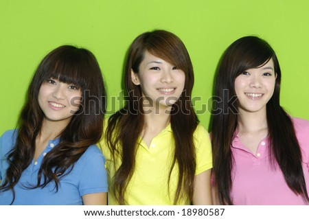 three happy girls a over green background - stock photo