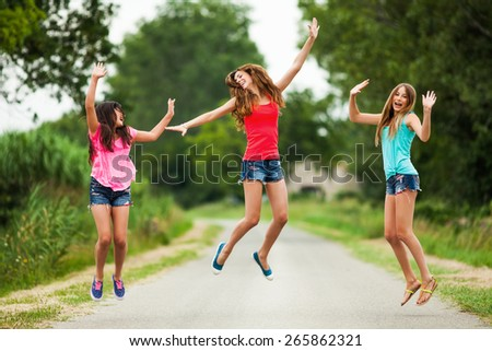 Three happy girls jumping - stock photo