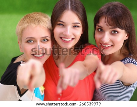 Three happy girls pointing fingers at you choosing - stock photo