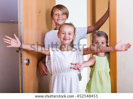 Three happy joyful children standing at house entrance and smiling - stock photo
