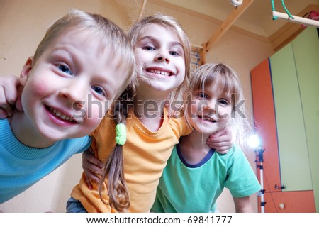 three happy kid in a domestic sports room - stock photo