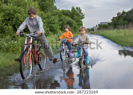Three happy kids are going through a puddle