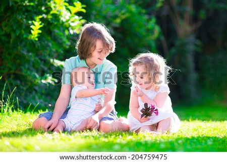 Three happy kids, brothers and sister, laughing teenager boy, little baby and a funny curly girl playing together with flowers in a sunny garden of their backyard  on a warm sunny day - stock photo