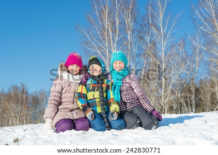 Three happy kids having fun in winter park - stock photo
