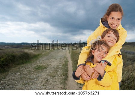 Three happy kids in raincoats on the country - stock photo