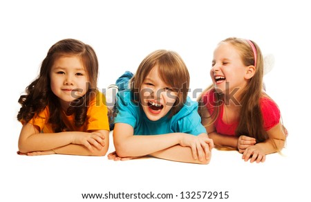 Three happy kids laying on the floor in a line together smiling and laughing, isolated on white - stock photo