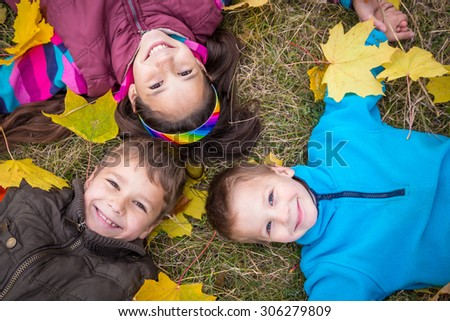 Three happy kids lying together on withered grass with fallen leaves, outdoors - stock photo