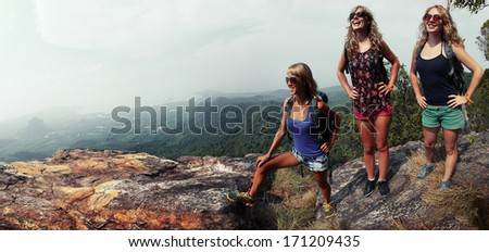 Three happy ladies with backpacks standing on top of a mountain and enjoying valley view - stock photo