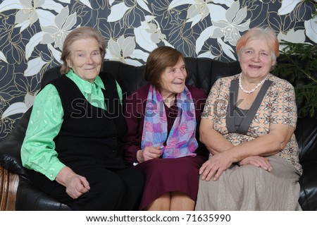 Three happy mature ladies sitting and laughing on a couch