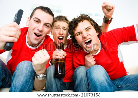 Three happy men sitting on couch and watching sport on TV. - stock photo